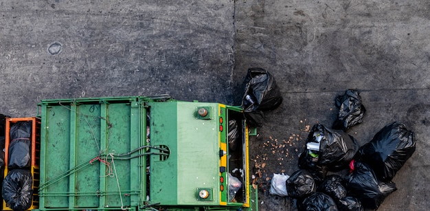 Green garbage truck collecting a large number of black garbage bags