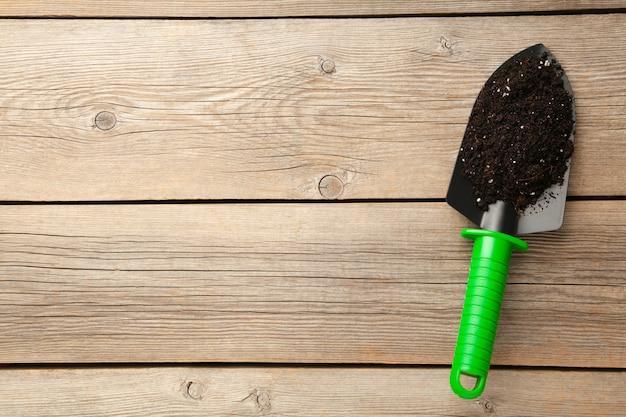 녹색 정원 도구 삽과 회색 나무 배경에 토양
