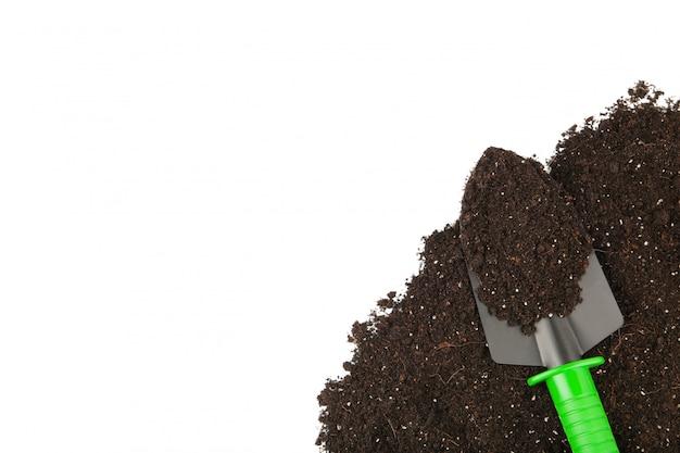 Green garden tools shovel and soil isolated Premium Photo