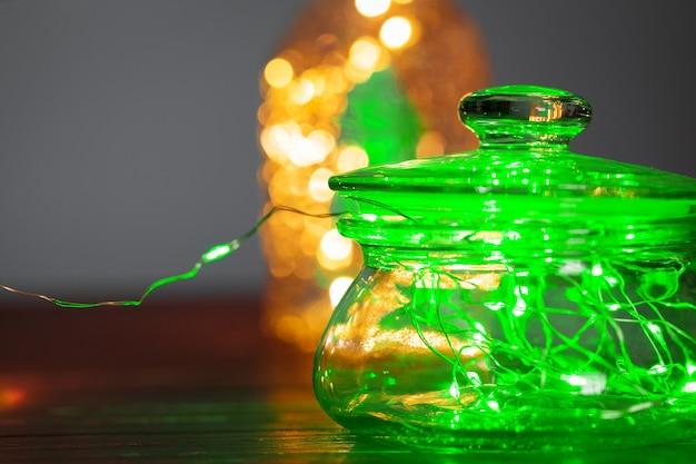 Green garland with light bulbs put in glass storage jar