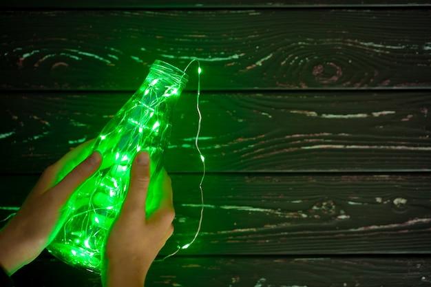 유리 저장 용기에 전구를 넣은 녹색 화환