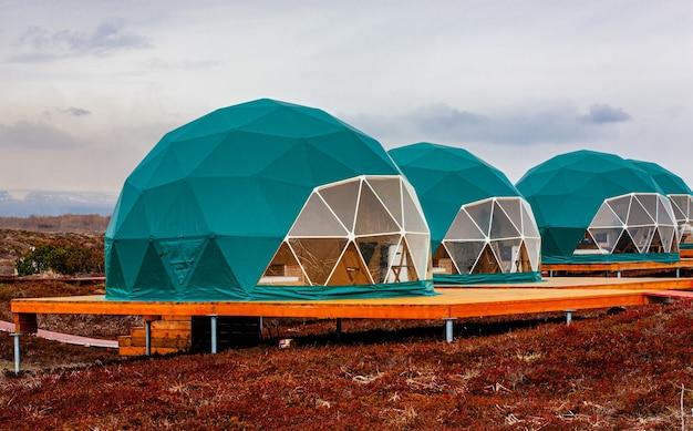 カムチャツカ半島の緑のジオドームテント。居心地の良い、キャンプ、グランピング、休日、休暇のライフスタイルのコンセプト。屋外キャビン、風光明媚な背景