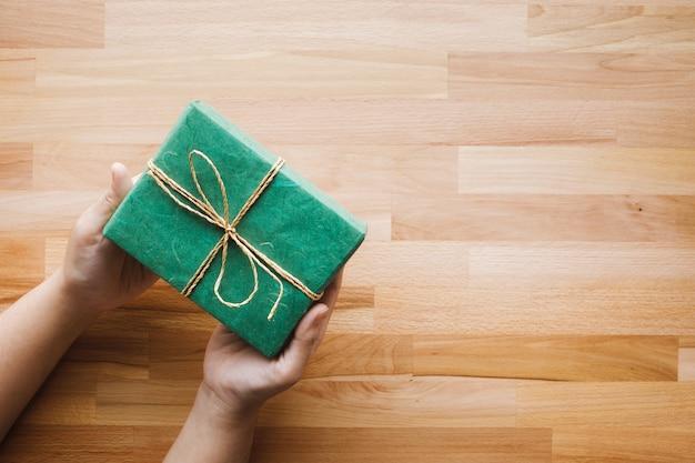 木製の背景を持つ女の子の手に緑のギフトボックス