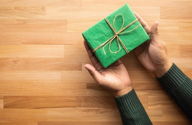 나무 테이블에 남성 손에 녹색 선물 상자