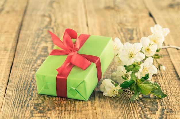 木製の背景に美しいジャスミンの花の枝と緑のギフトボックス。休日に贈り物をするという概念。