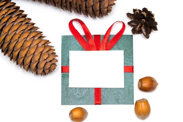 Зеленый подарок с красной лентой и изолированными шишками