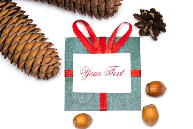 白い背景の上の赤いリボンと松ぼっくりと緑の贈り物