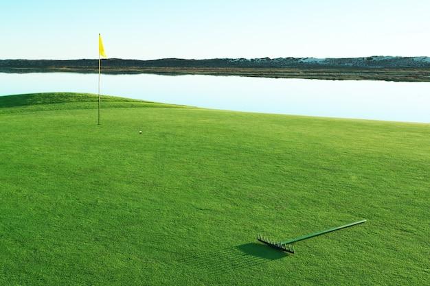 Зеленая поляна для гольфа и грабли по песку.