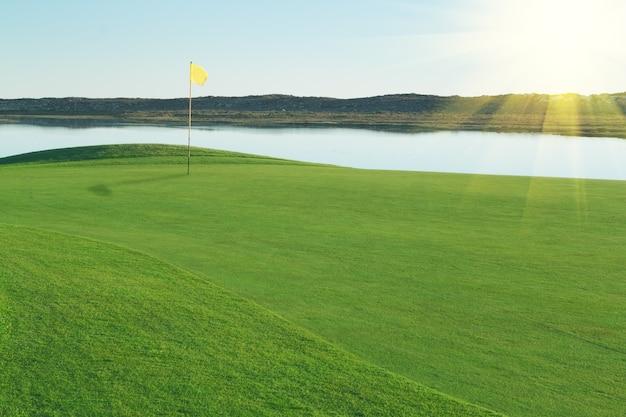 Поле для гольфа на зеленой поляне, с желтым флагом.