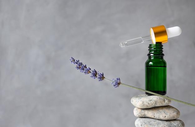 돌과 라벤더 장식에 녹색 유리 병.