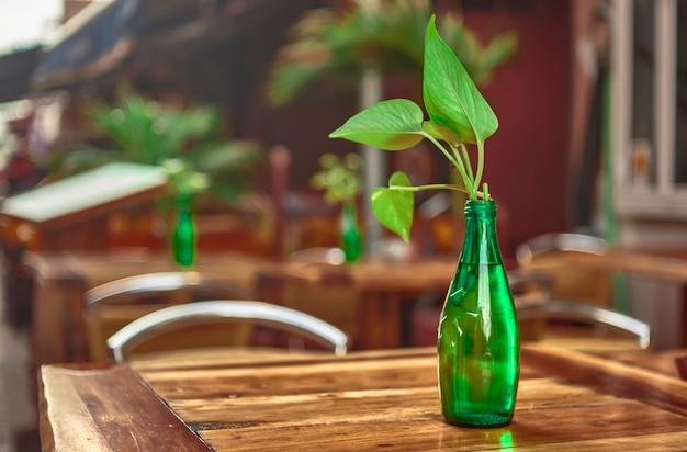 Зеленая стеклянная бутылка на столе с листом. декоративный элемент.