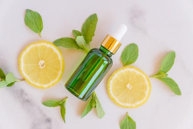 ピペット、大理石の背景にミントの葉とレモンのスライスと緑のガラス瓶