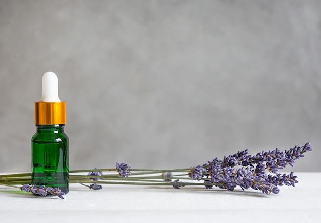 흰색 나무 테이블에 라벤더 오일과 라벤더 잔가지가 있는 녹색 유리병