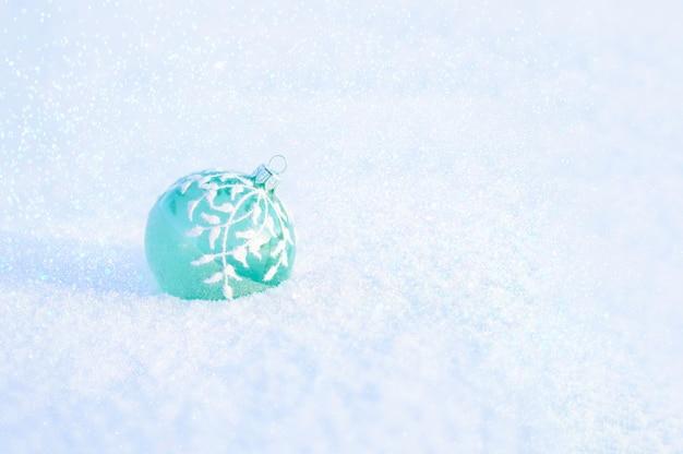 Елочный шар зеленого стекла на белом снегу