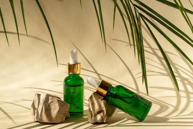 石と熱帯の葉とベージュの表面にスポイトが付いている緑色のガラス化粧品ボトル