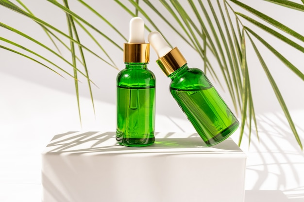 Green glass cosmetic bottles with a dropper on a white podium with tropical leaves