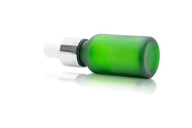 Зеленая стеклянная бутылка с сывороткой-капельницей на белом фоне, макет для дизайна косметической продукции