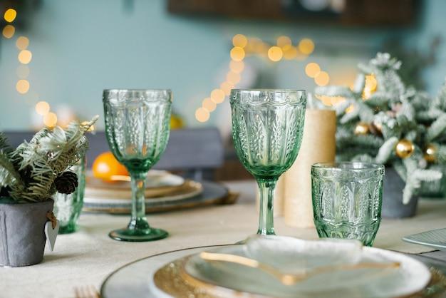 お祝いのクリスマスディナーのための緑色のガラスグラス