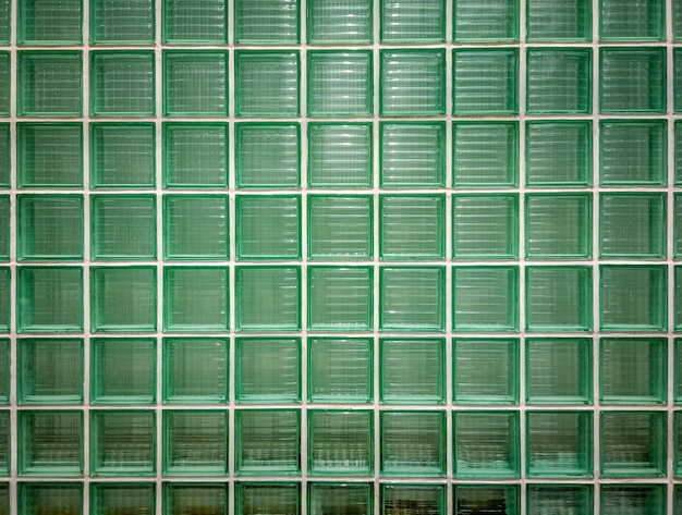 Green glass wall background. wall of shiny tiled glass blocks in green.