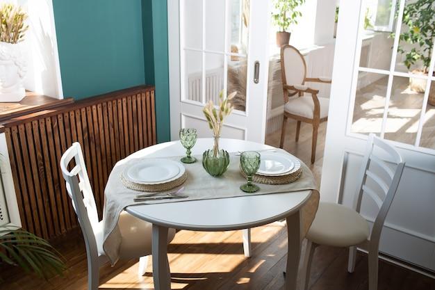 Зеленые стаканы и белая посуда на кухонном столе, с зеленым растением в гостиной на заднем плане.