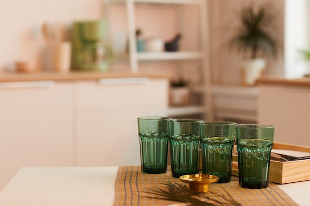 Green glasses on kitchen table in minimal interior, ready for serving
