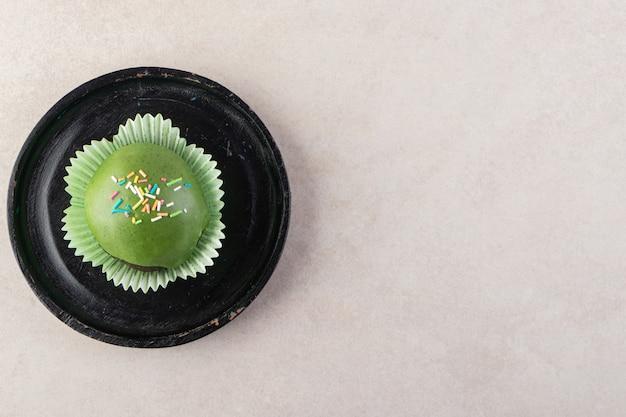 ベージュのテーブルの上に振りかける緑の艶をかけられたカップケーキ。