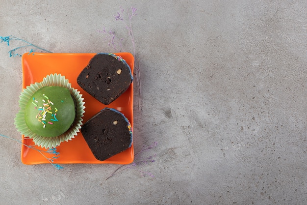 ベージュのテーブルに振りかける緑の艶をかけられたカップケーキ。