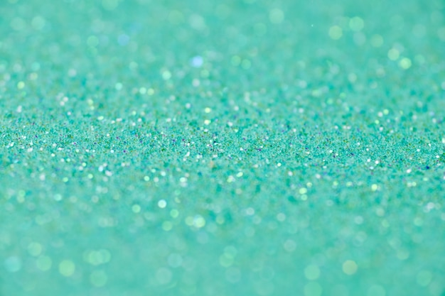 Green glitter texture. new year or christmas background for greeting card. valentines day celebration. shiny sparkle design for festive decoration: wedding, holiday or anniversary party.