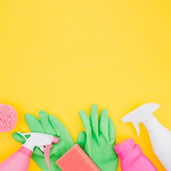 Green gloves; spray bottle; sponge and detergent bottles on yellow backdrop