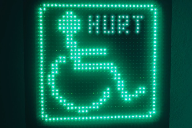 Green glowing symbol of the disabled hanging on the wall