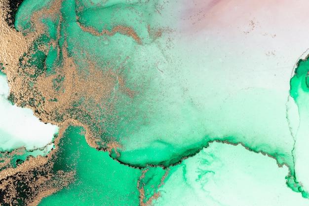 紙に大理石の液体インクアート絵画のグリーンゴールドの抽象的な背景。