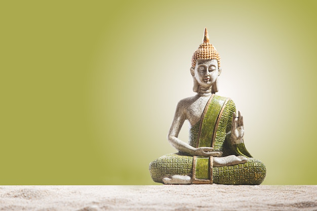 Green and golden buddha statue, on sand. meditation, spirituality and zen concept.