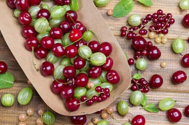 紙皿にグリーングーズベリーとチェリー。テーブルの上のベリーとミントの葉。木製の背景。フラットレイ