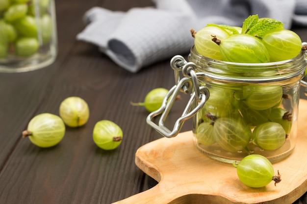 まな板のガラス瓶に緑色のグーズベリー。テーブルの上の灰色のナプキンとグーズベリー。暗い木製の背景。上面図