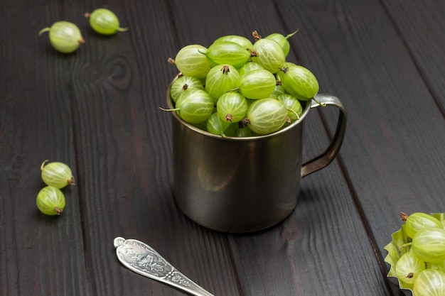 金属製マグカップの緑のグーズベリー。テーブルの上のベリー。上面図。木製の背景。