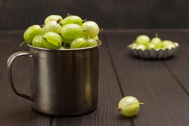 金属製マグカップの緑のグーズベリー。テーブルの上のベリー。木製の背景。