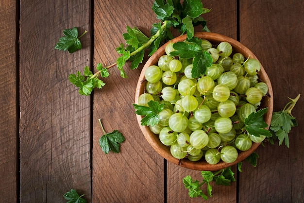 Green gooseberries in a wooden bowl
