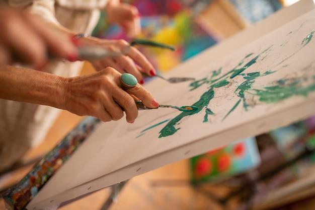 緑のガッシュ。絵を着色しながら緑のガッシュでペイントパレットを保持している高齢のアーティストのクローズアップ