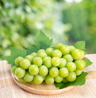 Green grape in bamboo basket on wooden table in garden