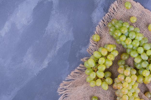緑のブドウは黄麻布の上に束ねられます。