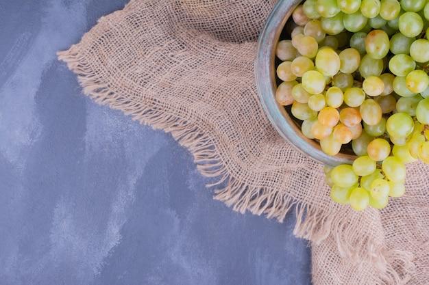 Грозди зеленого винограда на куске мешковины.
