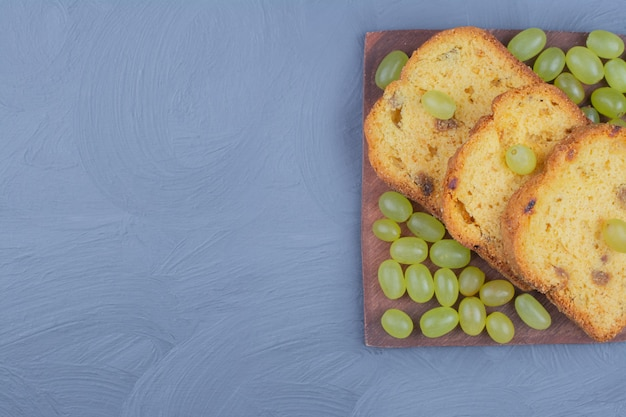 Torta di uva verde affettata su un piatto di legno