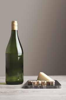 Зеленая бутылка сока виноградного вина возле каменной мраморной доски с деревянными буквами сыра и козьего сыра на белом фоне и столе