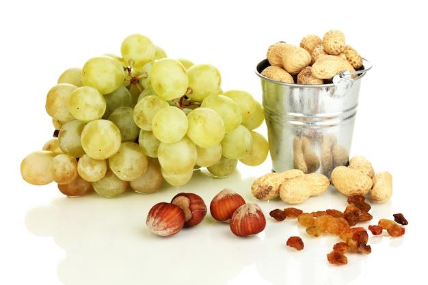 白に分離されたナッツと緑のブドウ
