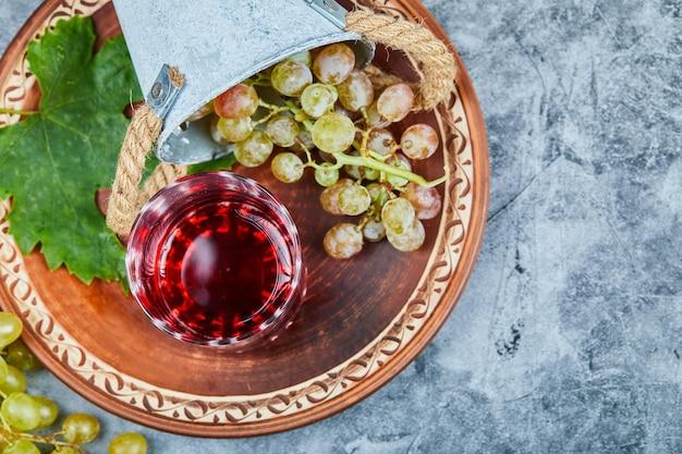 Зеленый виноград и бокал красного вина на столе.
