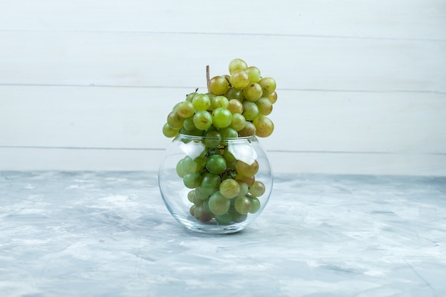 Green grapes in a glass pot side view on grungy grey and wooden background