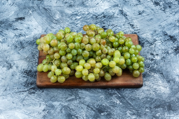 Green grapes on grungy grey and cutting board background. horizontal