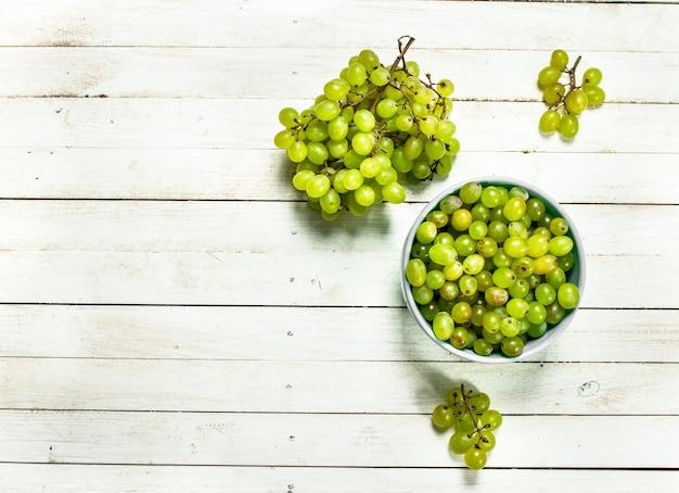 ボウルに緑のブドウ。白い木製のテーブルの上。