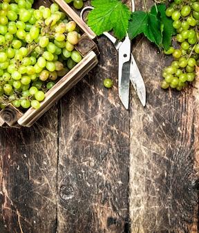 木製のテーブルの上の箱の中の緑のブドウ。