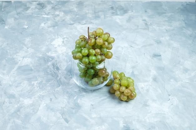 汚れた灰色の背景にガラスの鍋に緑のブドウ。ハイアングルビュー。